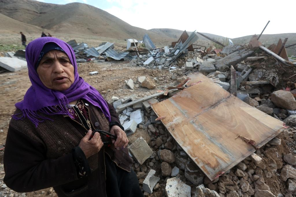 An elderly Palestinian woman stands near the rubble of her house after it was demolished by Israeli authorities on February 10, 2016 in the West Bank village of Jeftlek (AFP Photo/Jaafar Ashtiyeh)