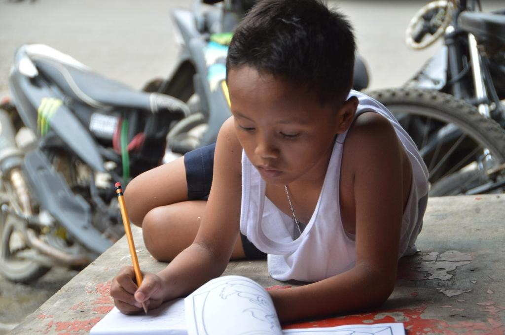 Daniel Cabrera, a nine-year-old homeless boy Filipino, does his homework on a pavement in Mandaue City, central Philippines (AFP Photo/)