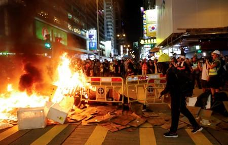 Protestors stand behind a burning barricade during a demonstration in Mong Kok district in Hong Kong