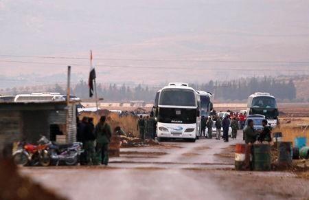 Rebels and civilians are seen next to coaches in which they will be evacuated, in Beit Jann, Syria December 29, 2017. REUTERS/Omar Sanadiki