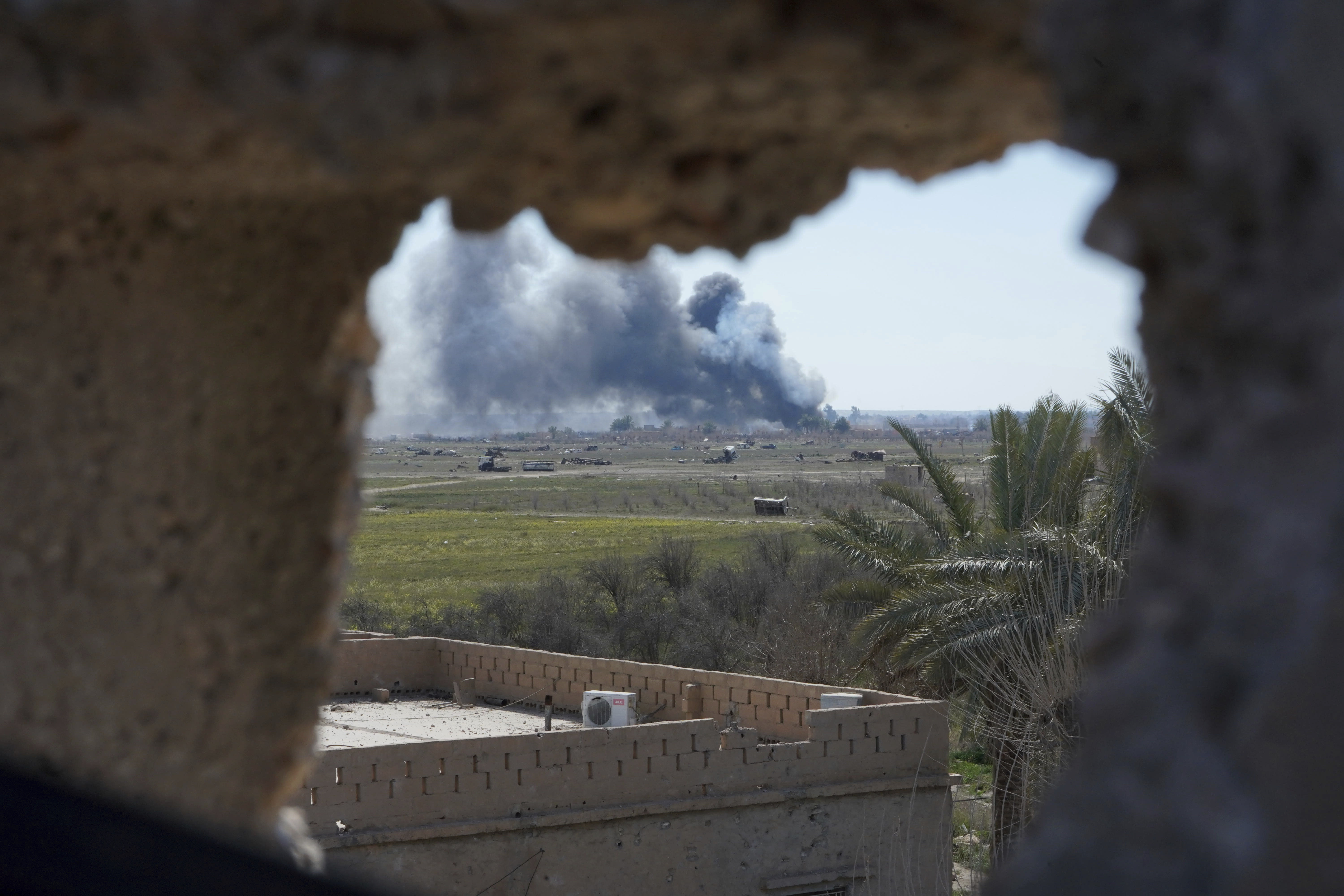 Columns of black smoke billow from the last small piece of territory held by Islamic State militants as U.S. backed fighters pounded the area with artillery fire and occasional airstrikes in Baghouz, Syria, Sunday, March 3, 2019. (AP Photo/Andrea Rosa)