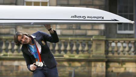 Britain's Olympic silver medallist rower, Grainger, walks under Edinburgh University's new eight man craft in Edinburgh, Scotland