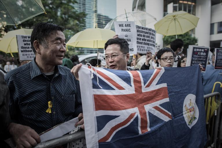 Pro-democracy demonstrators wave a colonial flag as they stage a rally outside the British consulate in the Admiralty district of Hong Kong, on November 21, 2014 (AFP Photo/Philippe Lopez)