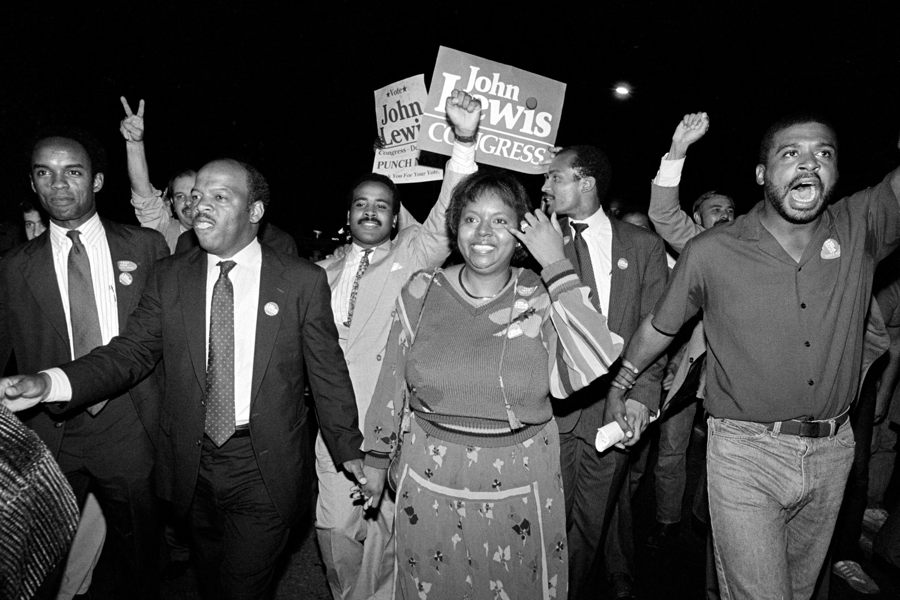 FILE - In this Tuesday night, Sept. 3, 1986, file photo, John Lewis, front left, and his wife, Lillian, holding hands, lead a march of supporters from his campaign headquarters to an Atlanta hotel for a victory party after he defeated Julian Bond in a runoff election for Georgia's 5th Congressional District seat in Atlanta. Lewis, who carried the struggle against racial discrimination from Southern battlegrounds of the 1960s to the halls of Congress, died Friday, July 17, 2020. (AP Photo/Linda Schaeffer, File)