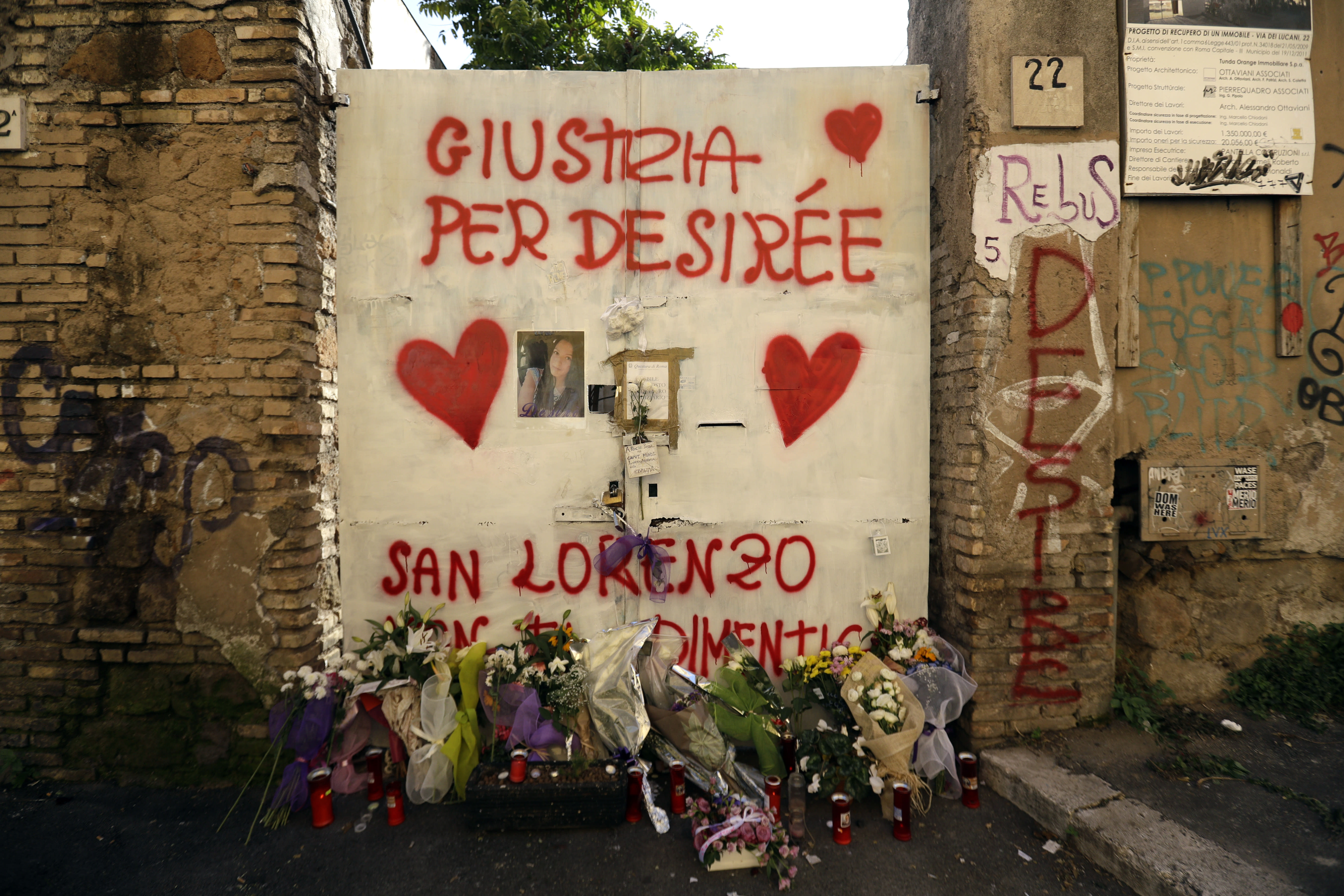 """Flowers lie by a writing on a door reading in Italian """"Justice for Desiree"""", outside the abandoned building where a 16-year-old girl was murdered, in Rome, Thursday, Oct. 25, 2018. Italian police have detained three suspects, all immigrants, in the slaying of a teenage girl who was drugged, gang-raped and left in an abandoned building known as a center for drug dealing in Rome. Authorities said Thursday that the three suspects, two Senegalese citizens and one Nigerian, were being held on suspicion of murder, group sexual assault and handing out drugs in the death late last week of 16-year-old Desiree Mariottini. (AP Photo/Gregorio Borgia)"""