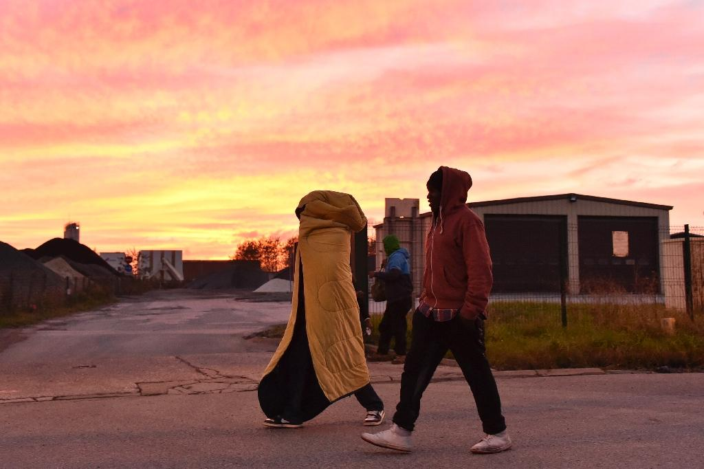 """Migrants walk at sunset near the """"Jungle"""" migrant camp in Calais, northern France, on October 27, 2016 (AFP Photo/Philippe Huguen)"""
