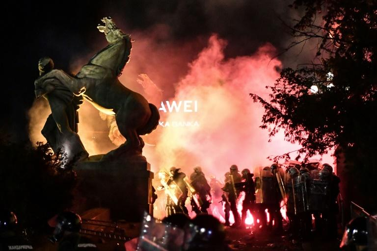 Police stand in tear gas smoke outside the National Assembly building in Belgrade, on July 10, 2020, during clashes with protesters at a demonstration against a weekend curfew announced to combat a resurgence of COVID-19 infections (AFP Photo/ANDREJ ISAKOVIC)