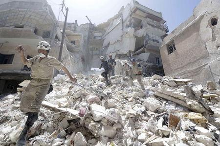 Civil defense members walk on rubble of a damaged site hit by what activists said was shelling on Tuesday by forces loyal to Syria's President Bashar al-Assad in Aleppo's al-Aryan neighborhood April 30, 2015. REUTERS/Hosam Katan