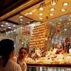 Gold inches lower as trade optimism, dovish ECB lift equities