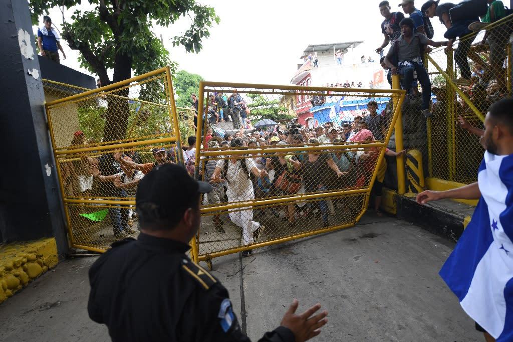 Honduran migrants tear down the gate of the Guatemala-Mexico international border bridge in Ciudad Hidalgo, Mexico (AFP Photo/Pedro Pardo )