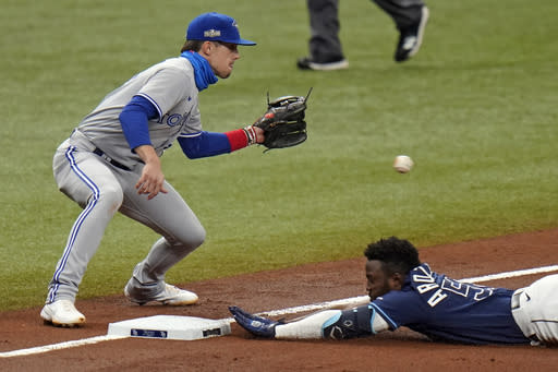 Tampa Bay Rays' Randy Arozarena slides into third base with a triple as Toronto Blue Jays' Cavan Biggio, left, waits for the throw during the fourth inning of Game 1 of a wild card series playoff baseball game Tuesday, Sept. 29, 2020, in St. Petersburg, Fla. (AP Photo/Chris O'Meara)