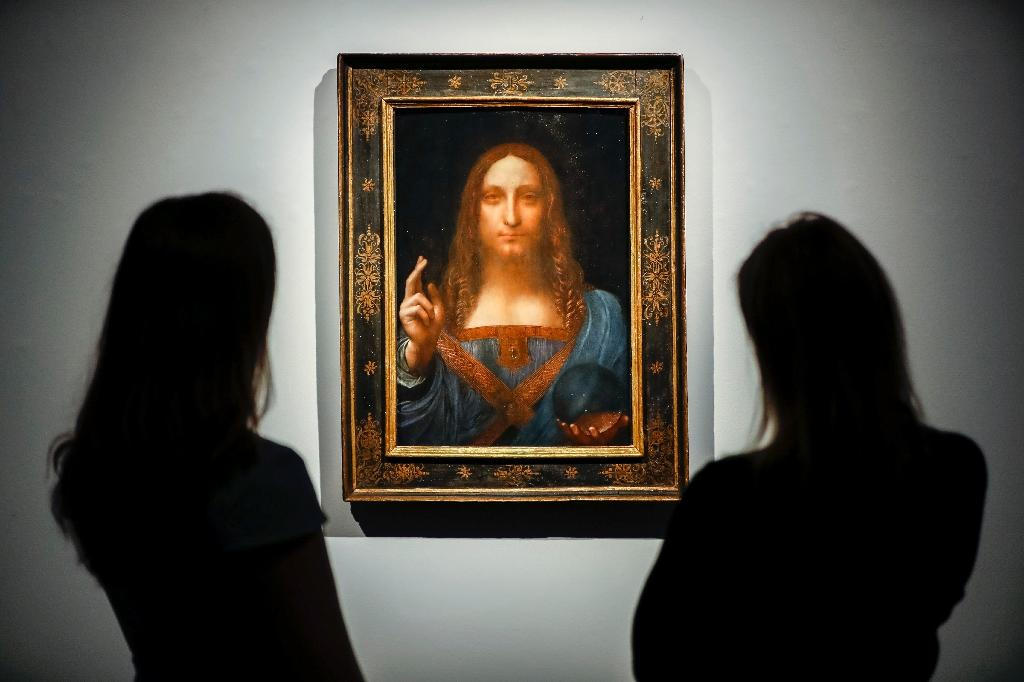 Christie's employees pose in front of a painting entitled Salvator Mundi and attributed to Leonardo da Vinci at a photocall at the auction house in central London on October 22, 2017 a month ahead of its sale (AFP Photo/Tolga Akmen)