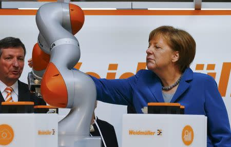 German Chancellor Merkel watches the work of KUKA robot during the opening tour at the Hannover Messe in Hanover