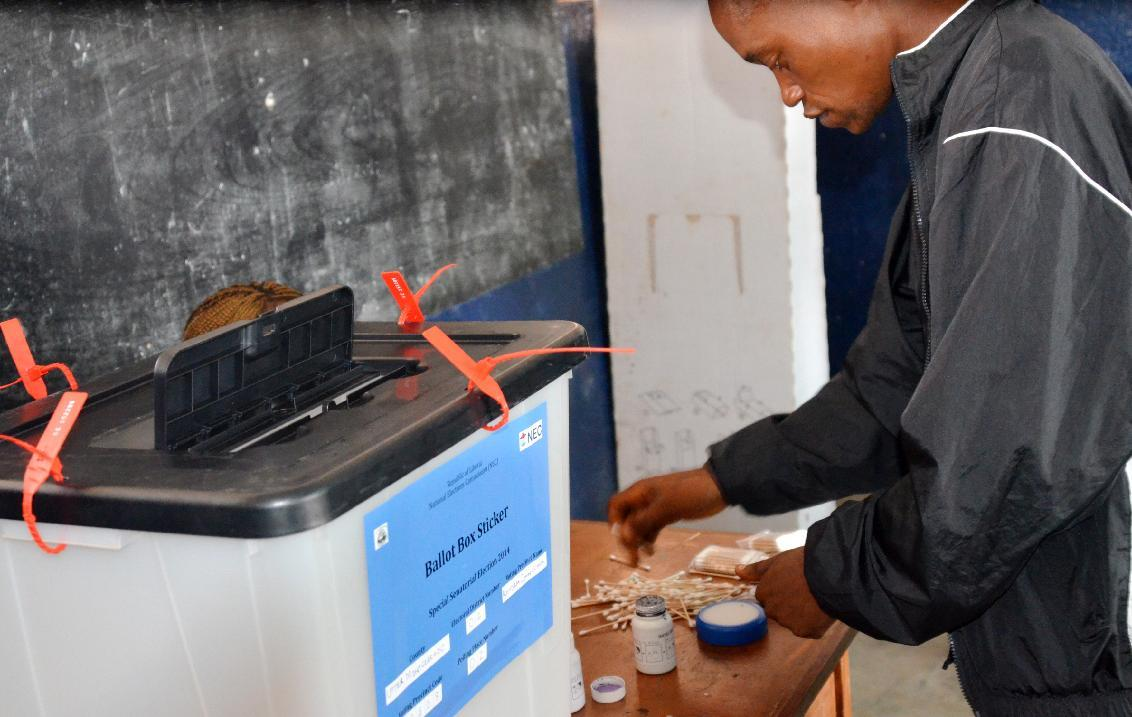 A polling agent prepares voting materials at a polling station in Monrovia on December 20, 2014 (AFP Photo/Zoom Dosso)