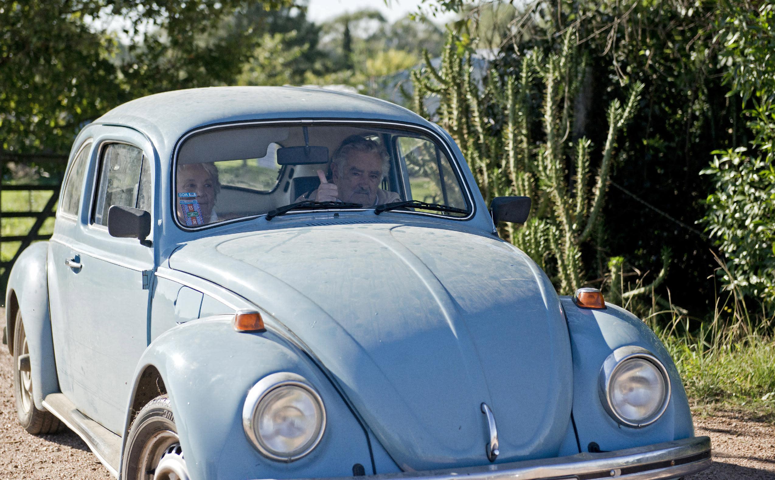 """El presidente de Uruguay José Mujica saluda con su pulgar derecho desde su automóvil cuando junto a su esposa, la senadora Lucia Topolansky, abandona su casa después de haber concedido una entrevista en su residencia en las afueras de Montevideo, Uruguay, el viernes 2 de mayo de 2014. Mujica en una entrevista exclusiva con The Associated Press defendió el viernes el plan para legalizar la marihuana de Uruguay y lo consideró mejor que el que se ha establecido en Colorado, Estados Unidos, donde según el mandatario, hay una gran """"hipocresía"""".(AP Photo/Matilde Campodonico)"""