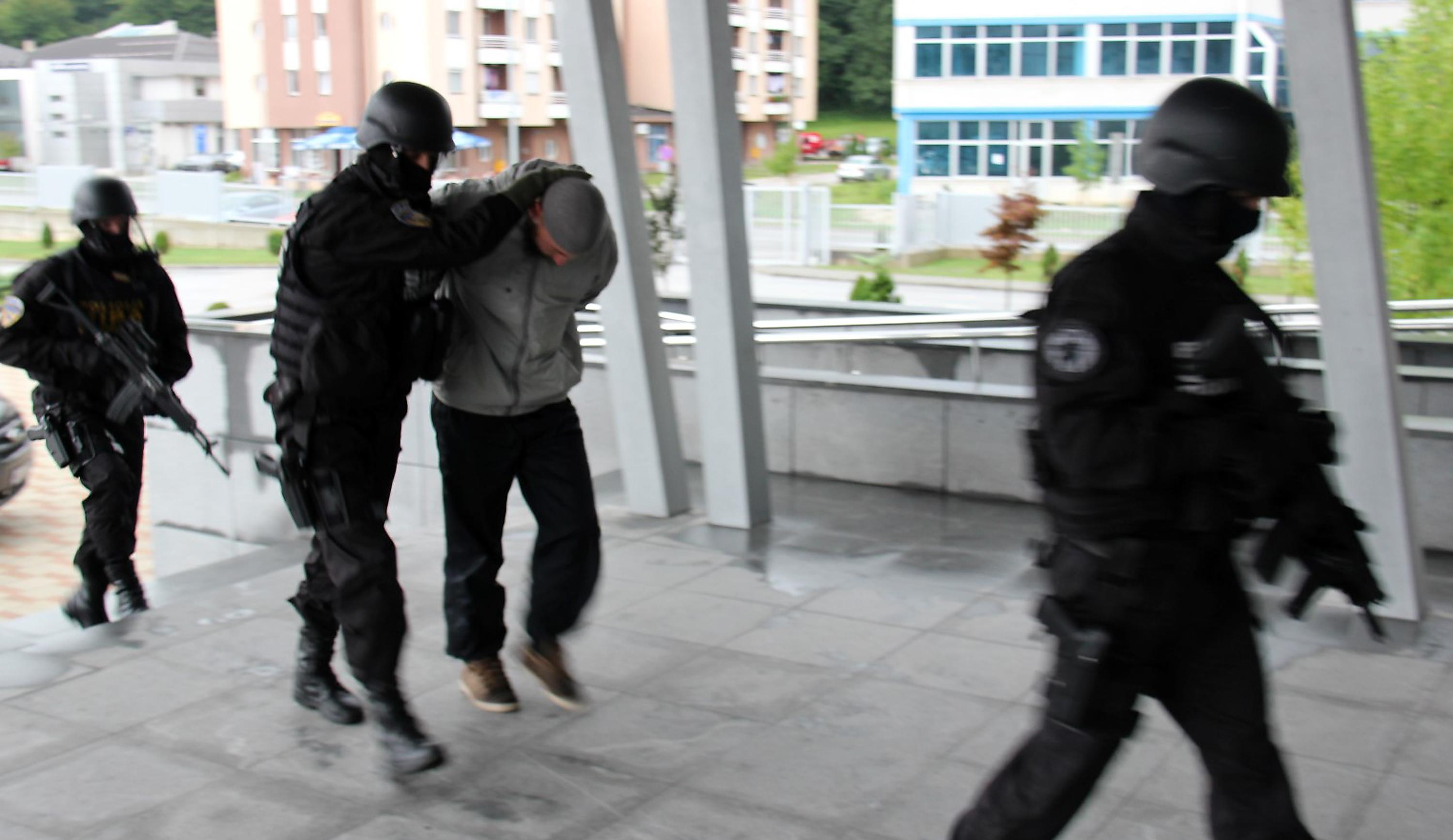 Bosnian police officers hold a man suspected of joining European-based Islamists and helping them travel to fight in Syria and Iraq, in Sarajevo, on September 3, 2014 (AFP Photo/)