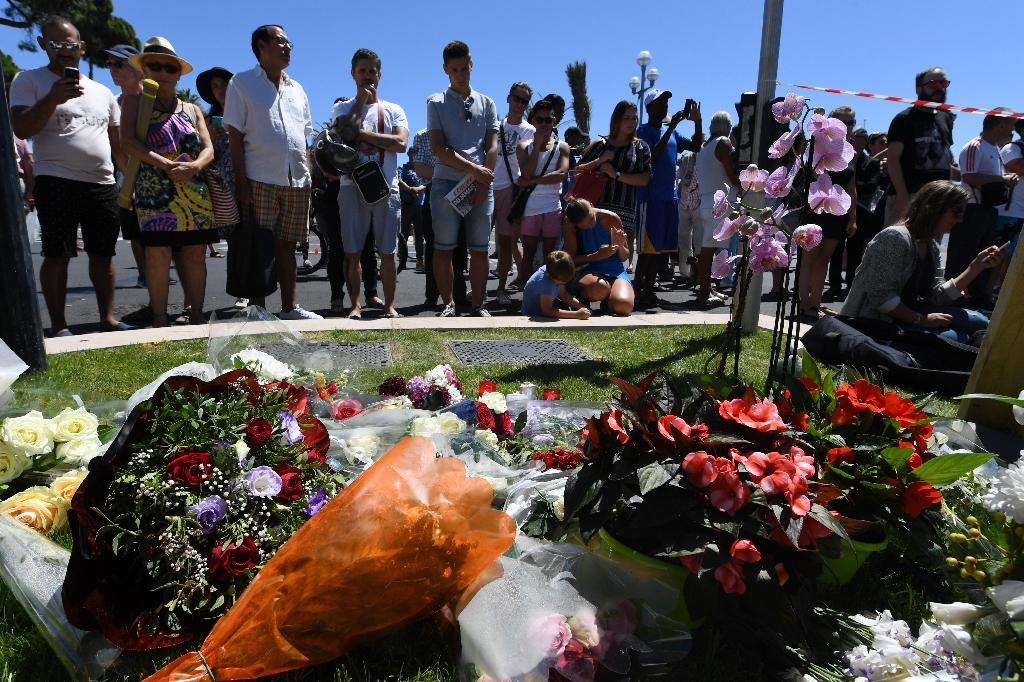 People stand in front of flowers and candles placed near the site in Nice where a gunman smashed a truck into a crowd of revellers celebrating Bastille Day, killing at least 84 people, on July 15, 2016 (AFP Photo/Boris Horvat)
