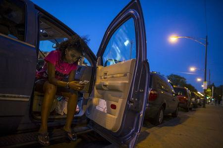 Mothers Against Senseless Killings (MASK) founder Tamar Manasseh checks her messages in her car in the Englewood neighborhood in Chicago, Illinois, United States, August 3, 2015. REUTERS/Jim Young