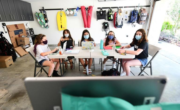 Seventh graders (from L) Mia Friedlander, Ella Kingsrud, Taylor Credle, Hannah Cooper and Bella Rocco follow instruction online by tutor Robin Lorch from an iPad placed on a ladder in a home garage on August 27, 2020 in Calabasas, California