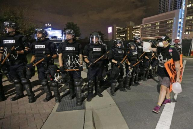 A protester walks in front of a line of police officers on Thursday, the third night of protests in Charlotte, N.C. (Photo: Chuck Burton/AP)
