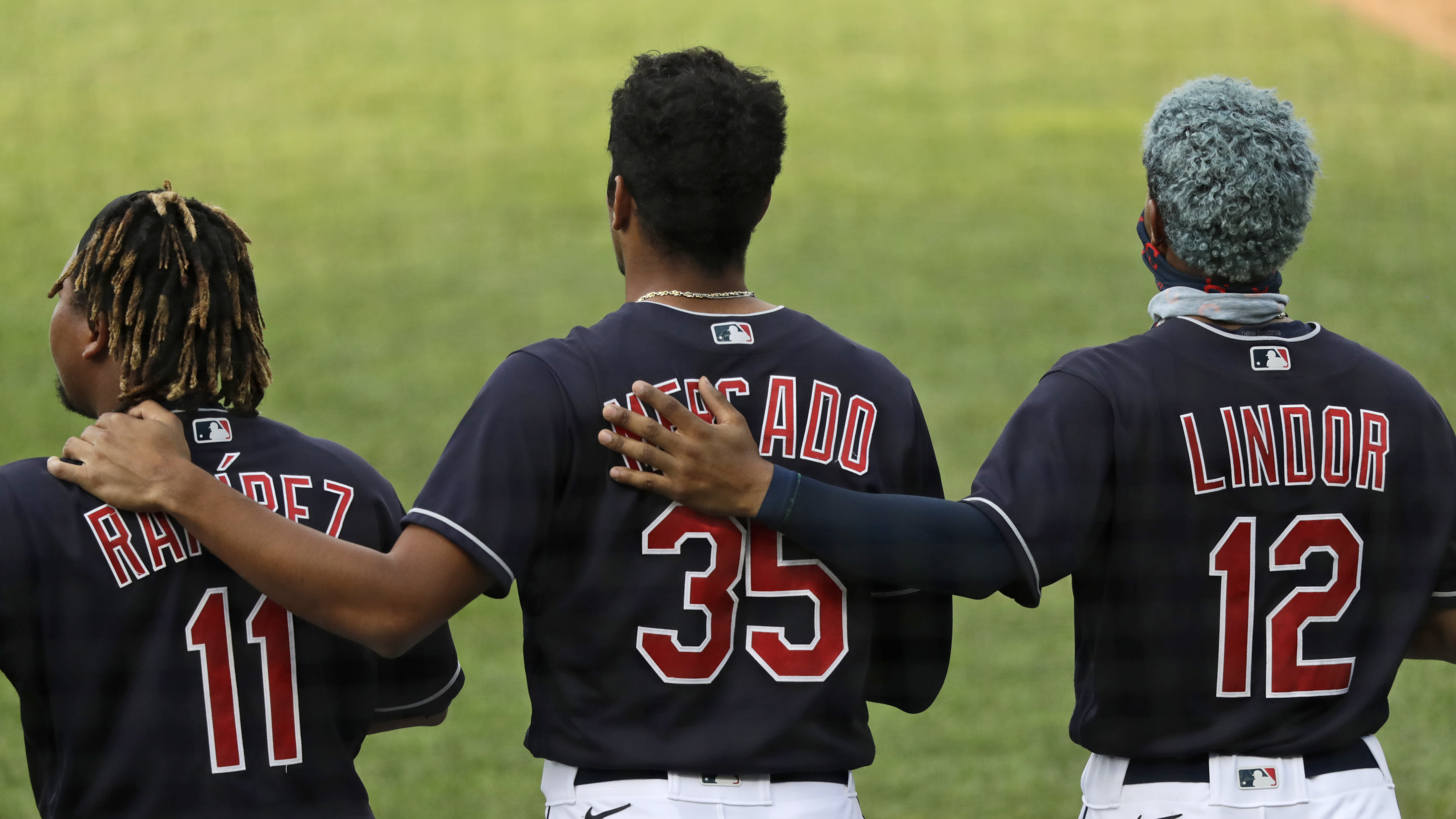 Members of the Cleveland Indians stand for the National Anthem before a preseason baseball game against the Pittsburgh Pirates, Monday, July 20, 2020, in Cleveland. (AP Photo/Tony Dejak)