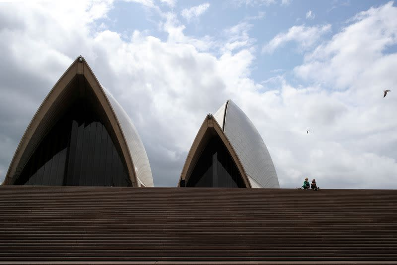 FILE PHOTO: Tourists sit on the mostly deserted steps of the Sydney Opera House