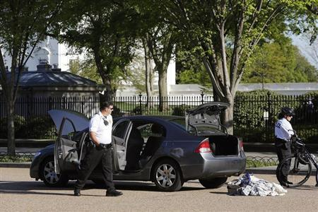 Members of the Uniformed Division of the Secret Service investigate an unauthorized vehicle outside the White House gates in Washington