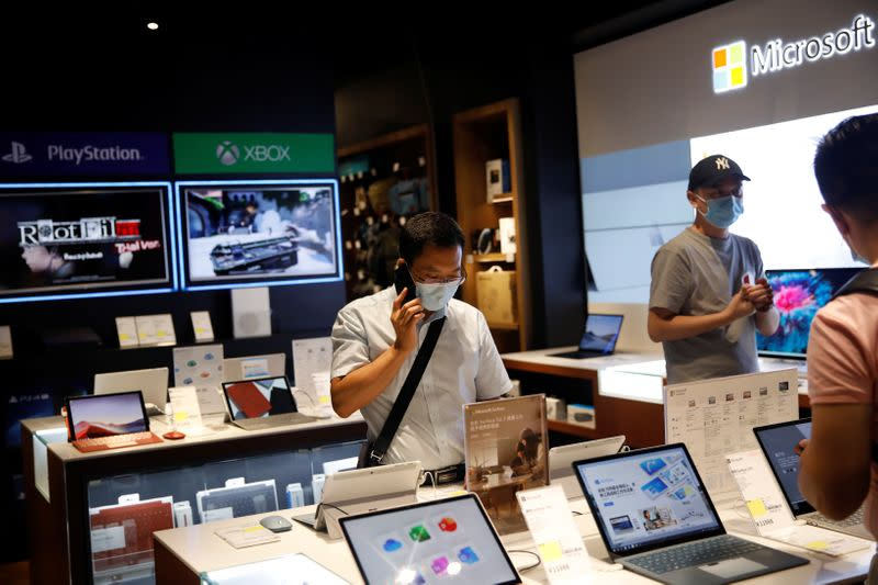 Men wearing face masks look at the merchandise on an electronics store at a shopping mall, in Beijing