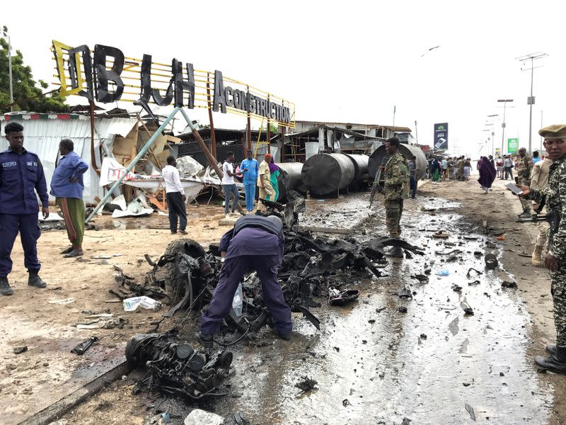 Somali security officers assess the wreckage of a car destroyed at the scene of an explosion in Mogadishu