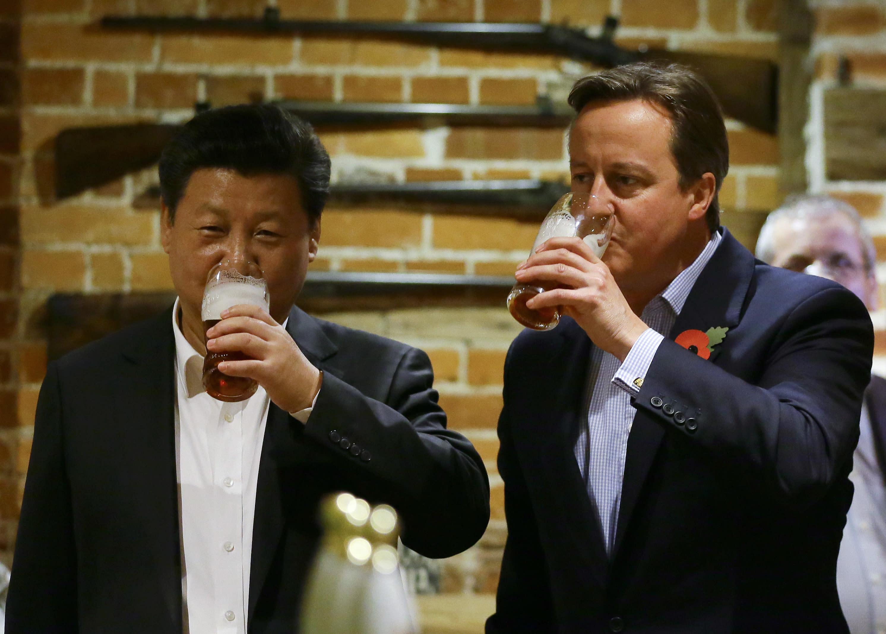 "FILE - In this Thursday, Oct. 22, 2015 file photo, Britain's Prime Minister David Cameron, right, drinks beer with Chinese President Xi Jinping, at a pub in Princess Risborough, near Chequers, England. Only five years ago, former British Prime Minister David Cameron was celebrating a ""golden era"" in U.K.-China relations, bonding with President Xi Jinping over a pint of beer at the pub and signing off trade deals worth billions. Those friendly scenes now seem like a distant memory, with hostile rhetoric ratcheting up this week over Beijing's new national security law on Hong Kong. China has threatened ""consequences"" after Britain offered refuge to millions in the former colony. (AP Photo/Kirsty Wigglesworth, file)"