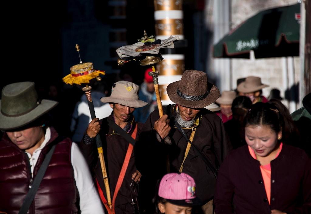 Pilgrims spin their prayer wheels outside the Jokhang Temple in the regional capital Lhasa, in China's Tibet Autonomous Region (AFP Photo/Johannes Eisele)