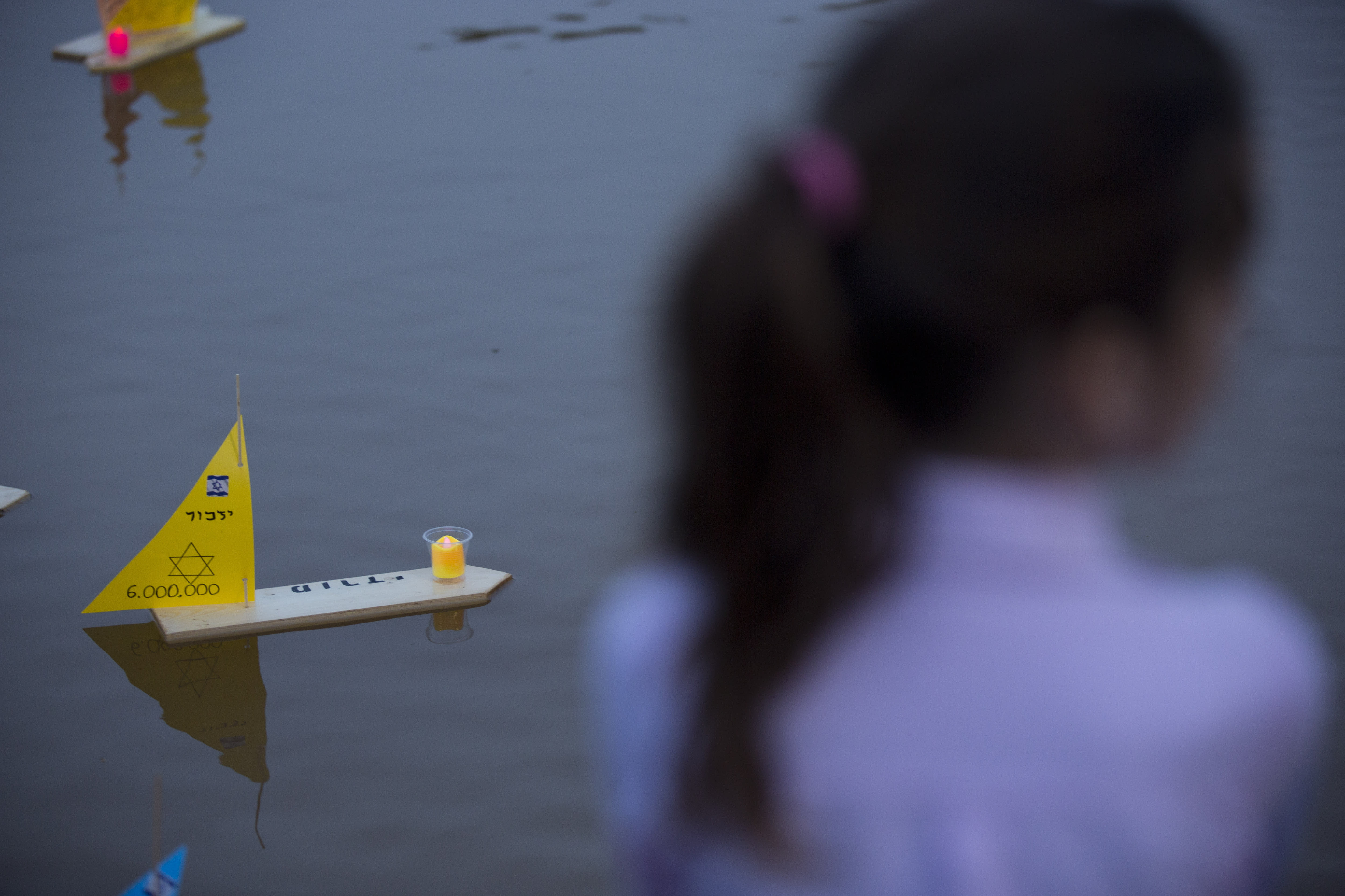 """Handmade boats with the names of Nazi concentration camps float in a lake during ceremony marking the annual Holocaust Remembrance Day in Tel Aviv, Israel, Wednesday, May 1, 2019. Israel marking the annual Day of Remembrance for the six million Jewish victims of the Nazi genocide who perished during World War II. Hebrew reads """"to remember"""". (AP Photo/Oded Balilty)"""