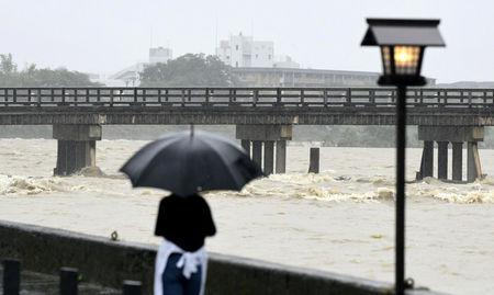 A local resident watches Togetsu Bridge and swollen Katsura River, caused by a heavy rain, in Kyoto, western Japan, in this photo taken by Kyodo July 6, 2018. Mandatory credit Kyodo/via REUTERS