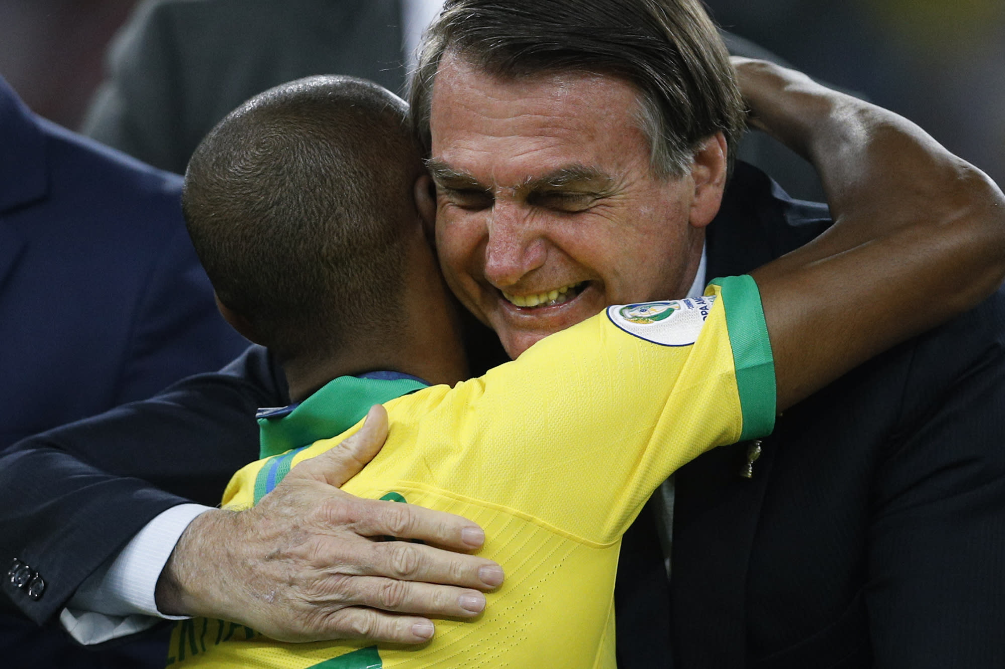 Brazil's President Jair Bolsonaro embraces Brazil's Fernandinho after he won the final soccer match of the Copa America against Peru at the Maracana stadium in Rio de Janeiro, Brazil, Sunday, July 7, 2019. (AP Photo/Victor R. Caivano)
