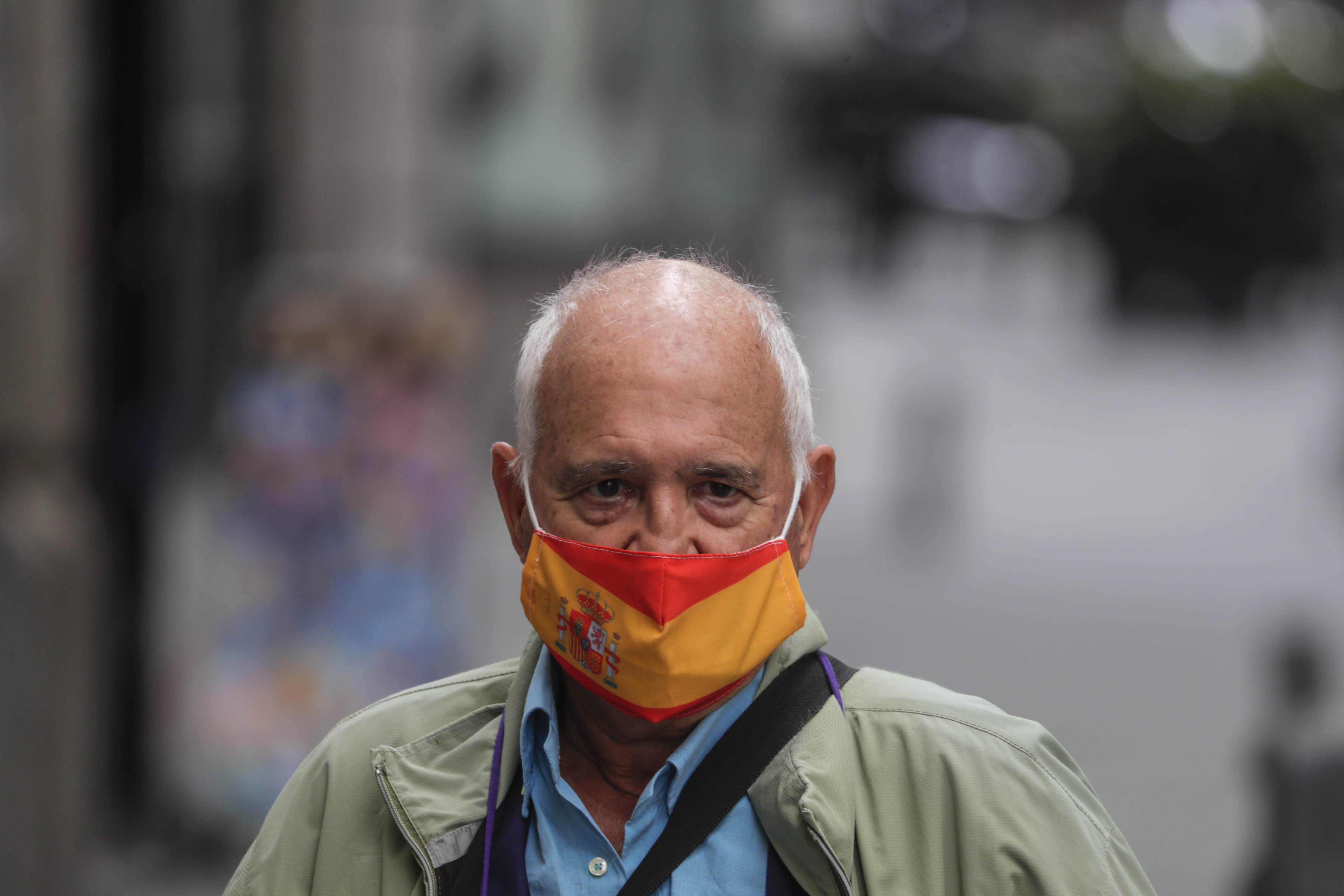 A man wearing a face mask to prevent the spread of coronavirus decorated with the Spanish flag stands in a street in downtown Madrid, Spain, Friday, Sept. 18, 2020. With more than 11,000 new daily coronavirus cases, the attention in Spain is focusing on its capital, where officials are mulling localized lockdowns and other measures to bring down the curve of contagion. (AP Photo/Manu Fernandez)