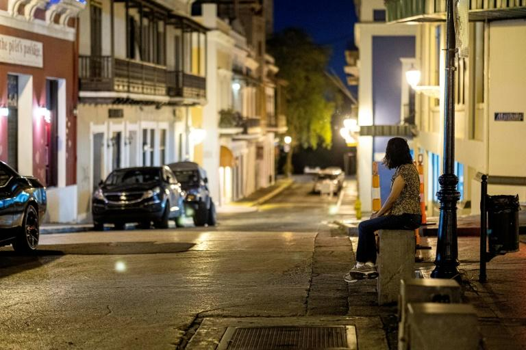A woman sits by herself in Old San Juan, Puerto Rico, at a normally busy area after Governor Wanda Vazquez told people to stay home (AFP Photo/Ricardo ARDUENGO)