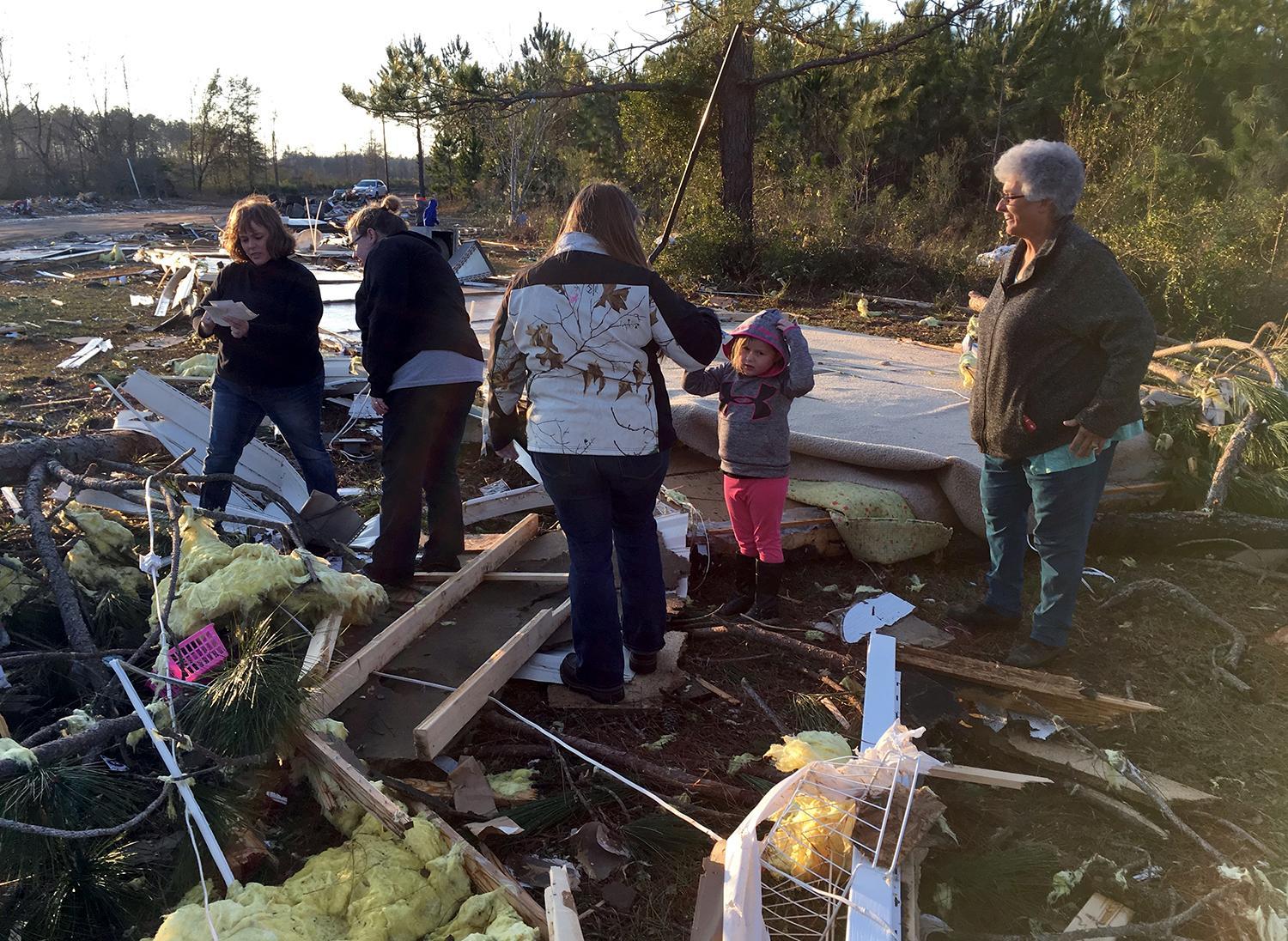 <p>Bonnie Collier, right, and her two granddaughters, daughter and daughter-in-law pick through the wreckage of her mobile home trying to find clothes and family photos on Monday, Jan. 23, 2017, near Cecil, Ga. (AP Photo/Brendan Farrington) </p>