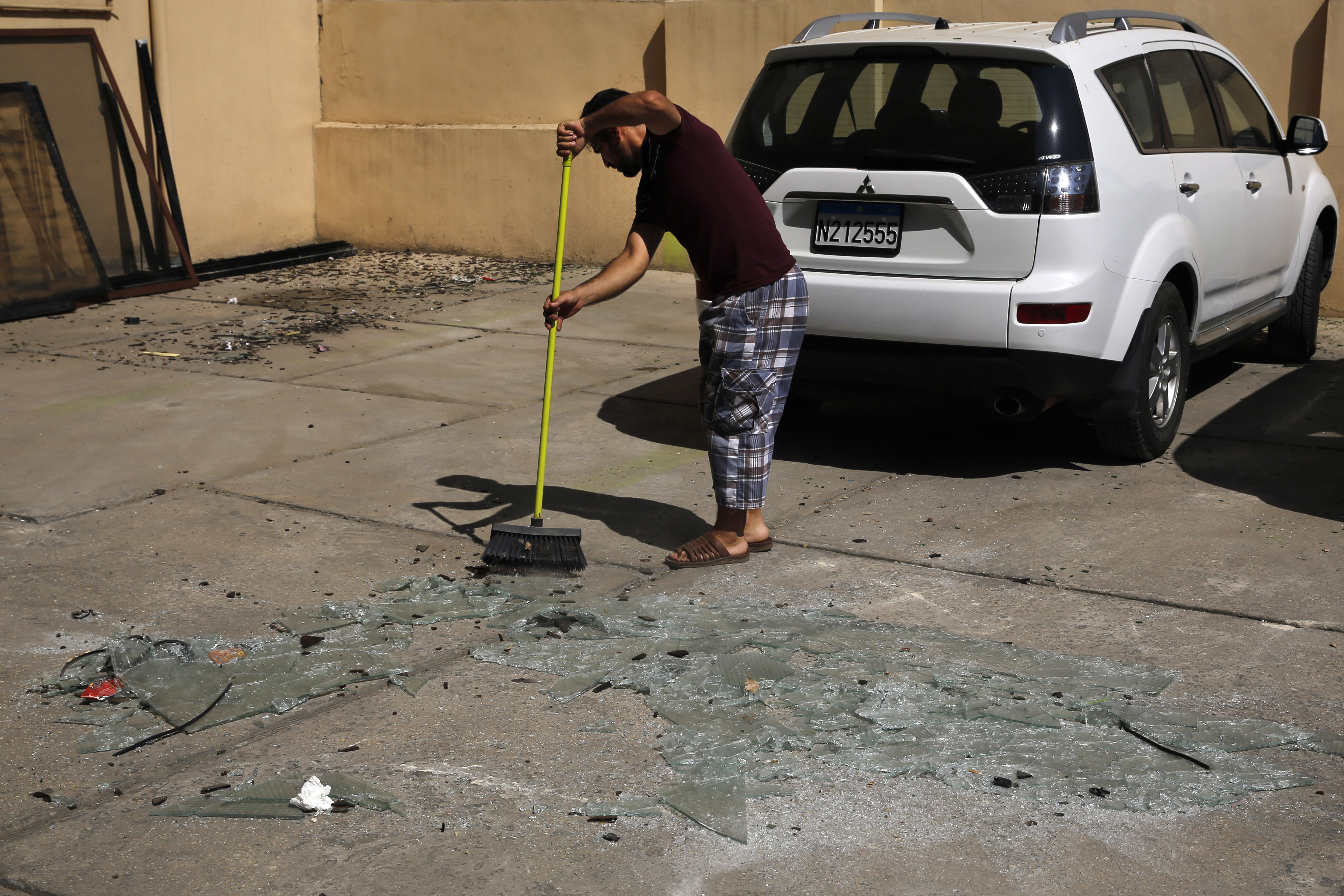 A man sweeps broken glass near the 11th-floor building that houses the media office in a stronghold of the Lebanese Hezbollah group, in a southern suburb of Beirut, Lebanon, Sunday, Aug. 25, 2019. Two Israeli drones crashed into the Hezbollah stronghold in the Lebanese capital overnight without the militants firing on them, a spokesman for the group said Sunday, saying the first fell on the roof of a building housing Hezbollah's media office while the second landed in a plot behind it. (AP Photo/Bilal Hussein)