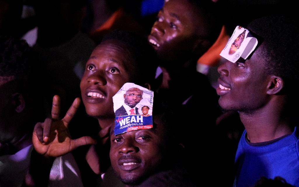 Hundreds of supporters of George Weah took to the streets of Monrovia, singing, dancing and embracing each other as news of his win in Liberia's presidential vote spread (AFP Photo/SEYLLOU)