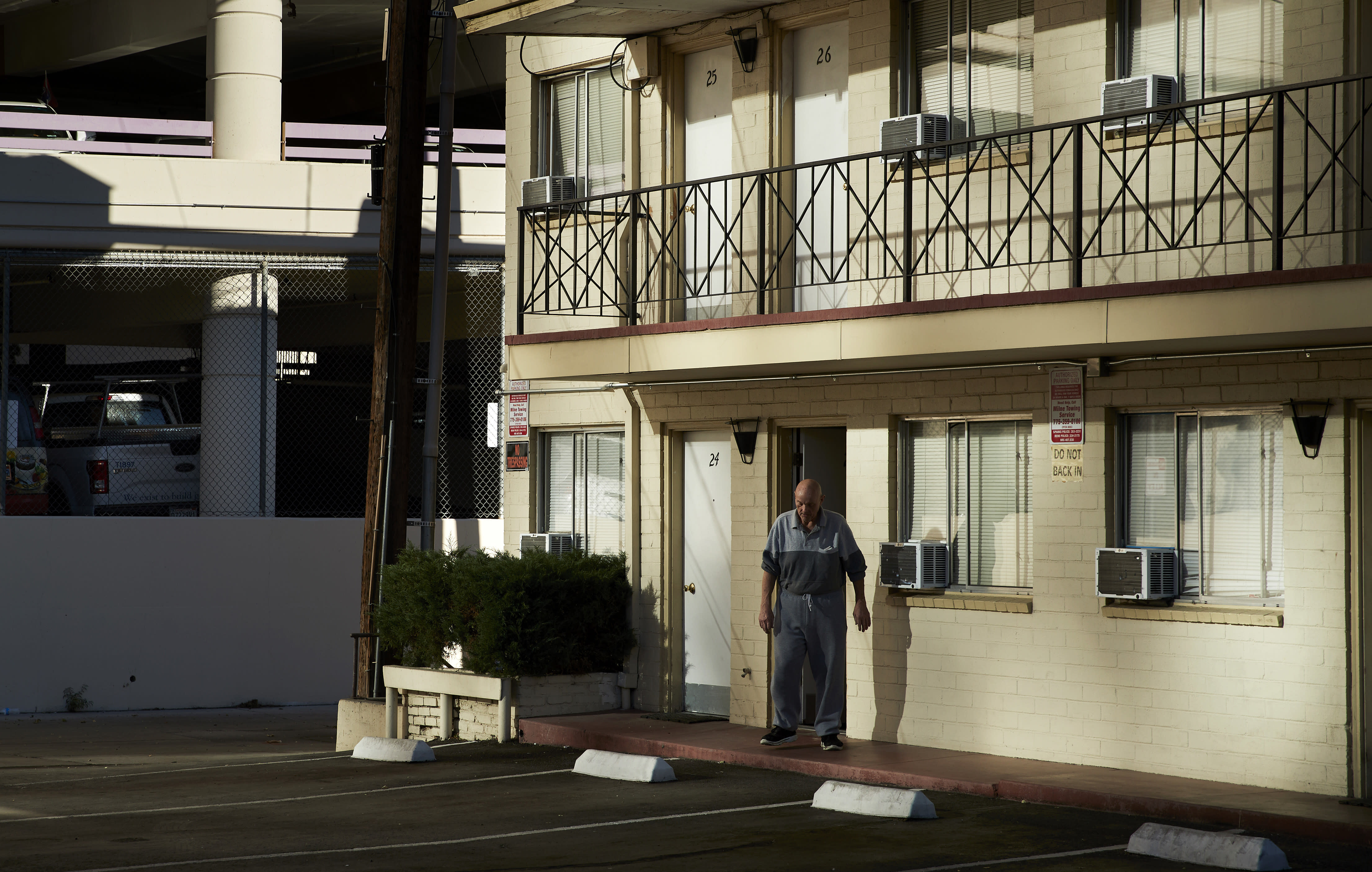 In this Oct. 12, 2018, photo, a man walks out of a weekly rental motel in Reno, Nev. The economic recovery has allowed Reno to reclaim its status as a boomtown, but that has been bad news for people on the margins who are having a harder time finding an affordable place to live, forcing many into the dozens of weekly rental motor lodges around the city. (AP Photo/John Locher)