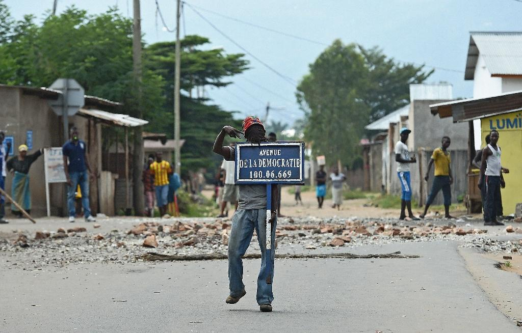 A protestor opposed to Burundian President Pierre Nkurunziza's third term holds a road sign reading 'Avenue of Democracy ' during a demonstration in Bujumbura on May 26, 2015 (AFP Photo/Carl de Souza)