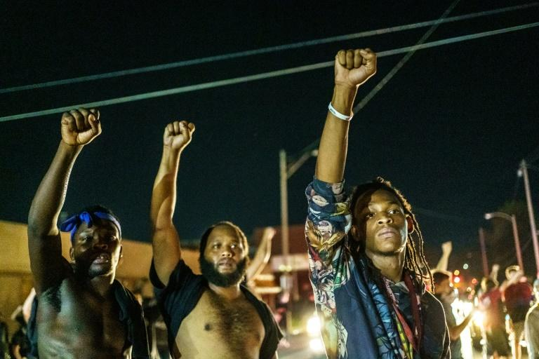 Protesters raise their fists during a demonstration against the shooting of Jacob Blake in Kenosha, Wisconsin in a fourth night of protests
