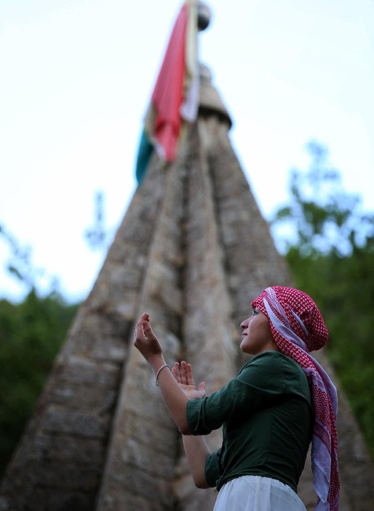 An Iraqi Yazidi raises her hands in prayer outside Lalish temple situated in a valley near Dohuk, 430 km (260 miles) northwest of Baghdad, during a ceremony to celebrate the Yazidi New Year, on April 14, 2015 (AFP Photo/Safin Hamed)