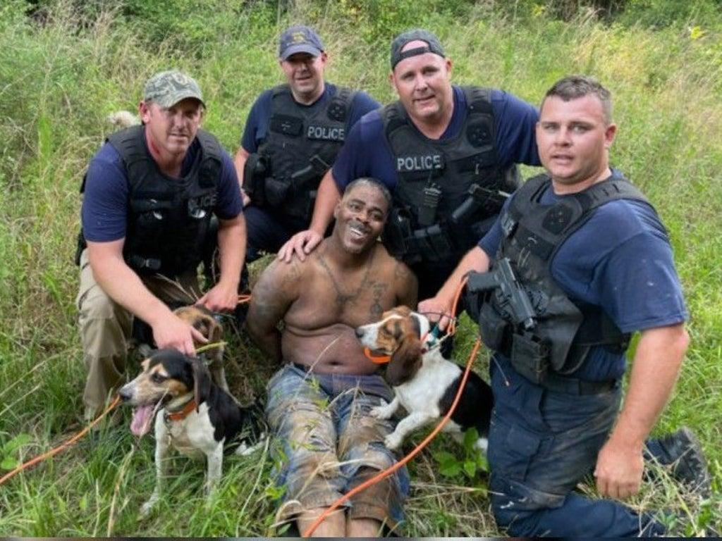 Anger as armed white police officers with dogs pose with captured Black suspect