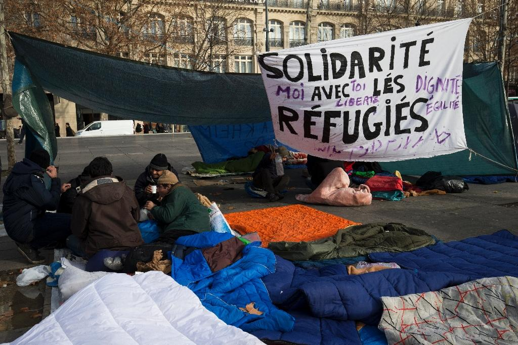 Dozens of refugees and migrants from several countries sit at a makeshift camp on the Place de la Republique square in Paris on January 4, 2016 (AFP Photo/Joel Saget)