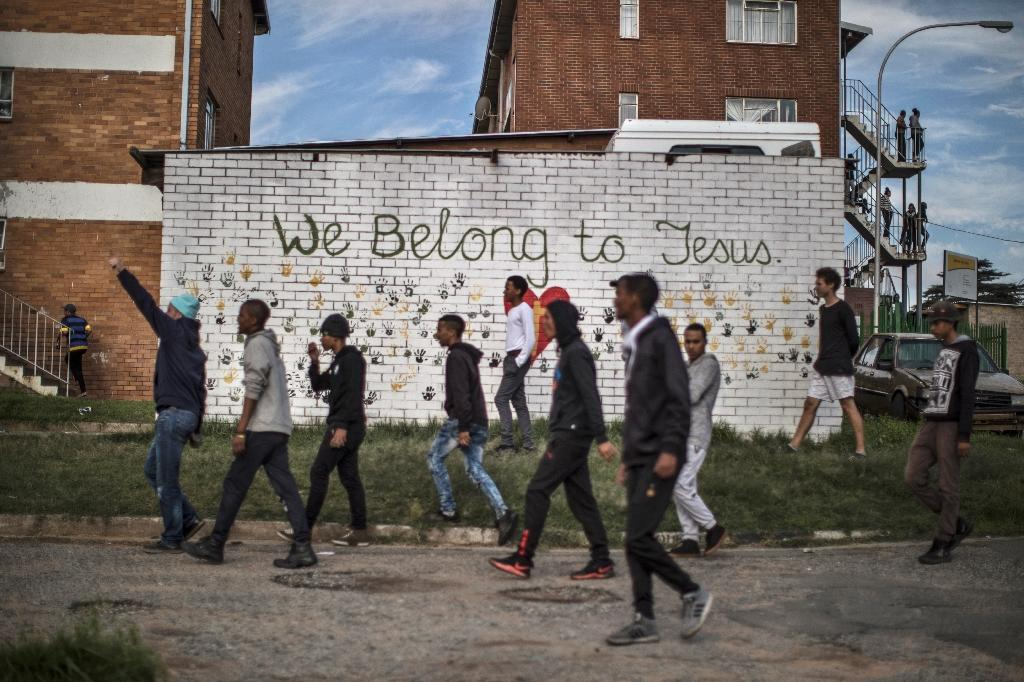 Protesters pass in front of a mural in Johannesburg as they faced off against police (AFP Photo/MARCO LONGARI)