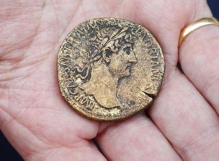 An archaeologist displays Roman Sestertius brass coin from around AD 30 with an image of the Emperor Hadrian which was dug out from the Crossrail site next to Liverpool Street Station in the City of London, in this file photo taken on August 7, 2013. REUTERS/Andrew Winning