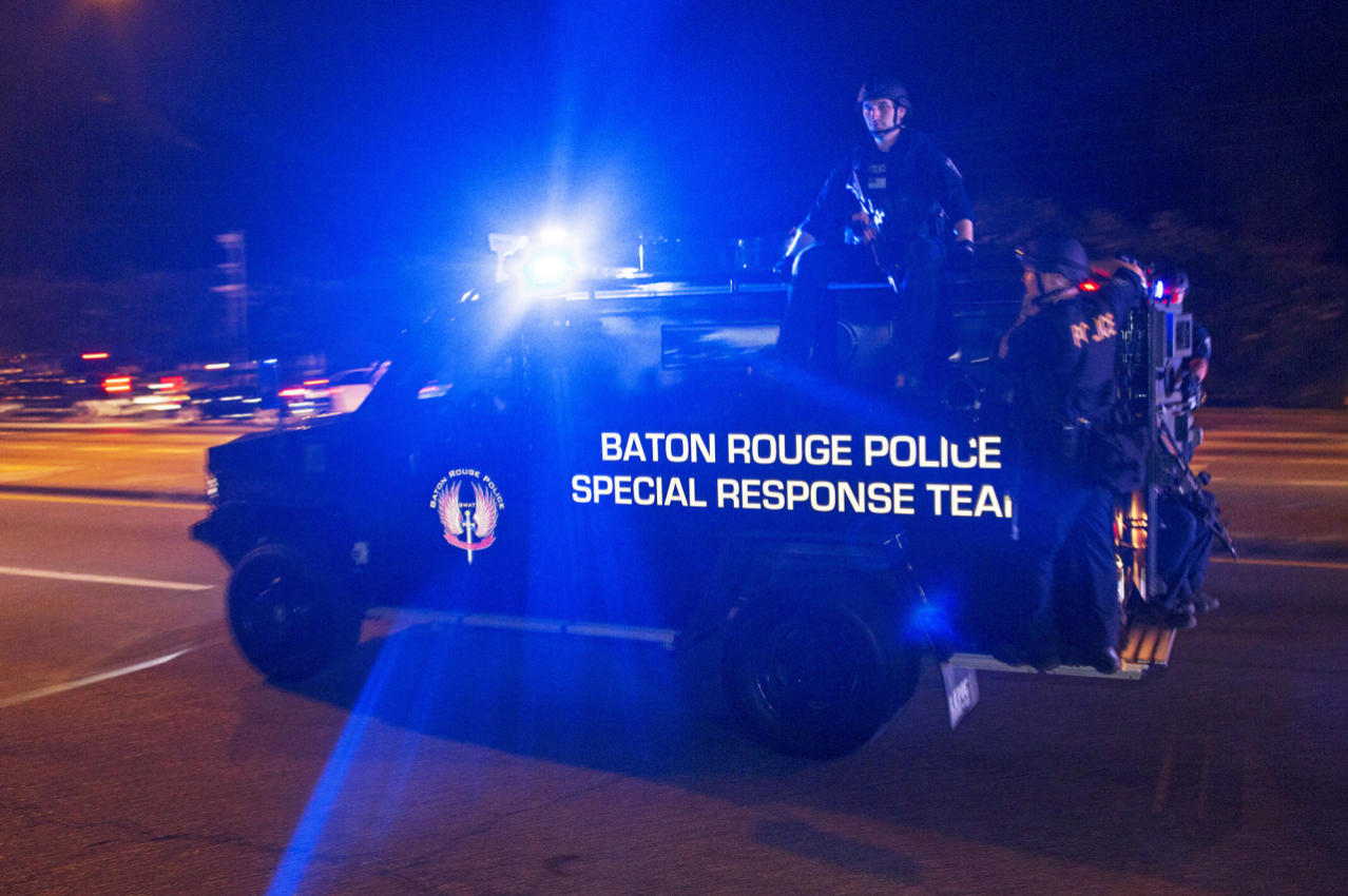 <p>Sheriff Deputies ride outside an armored vehicle on Airline Highway, a major road that passes in front of the Baton Rouge Police Department headquarters, as they attempt to clear protesters from the road in Baton Rouge, La., Saturday, July 9, 2016. People were protesting the shooting death of a black man, Alton Sterling, by two white police officers at a convenience store parking lot last week in Baton Rouge, La. (AP Photo/Max Becherer) </p>
