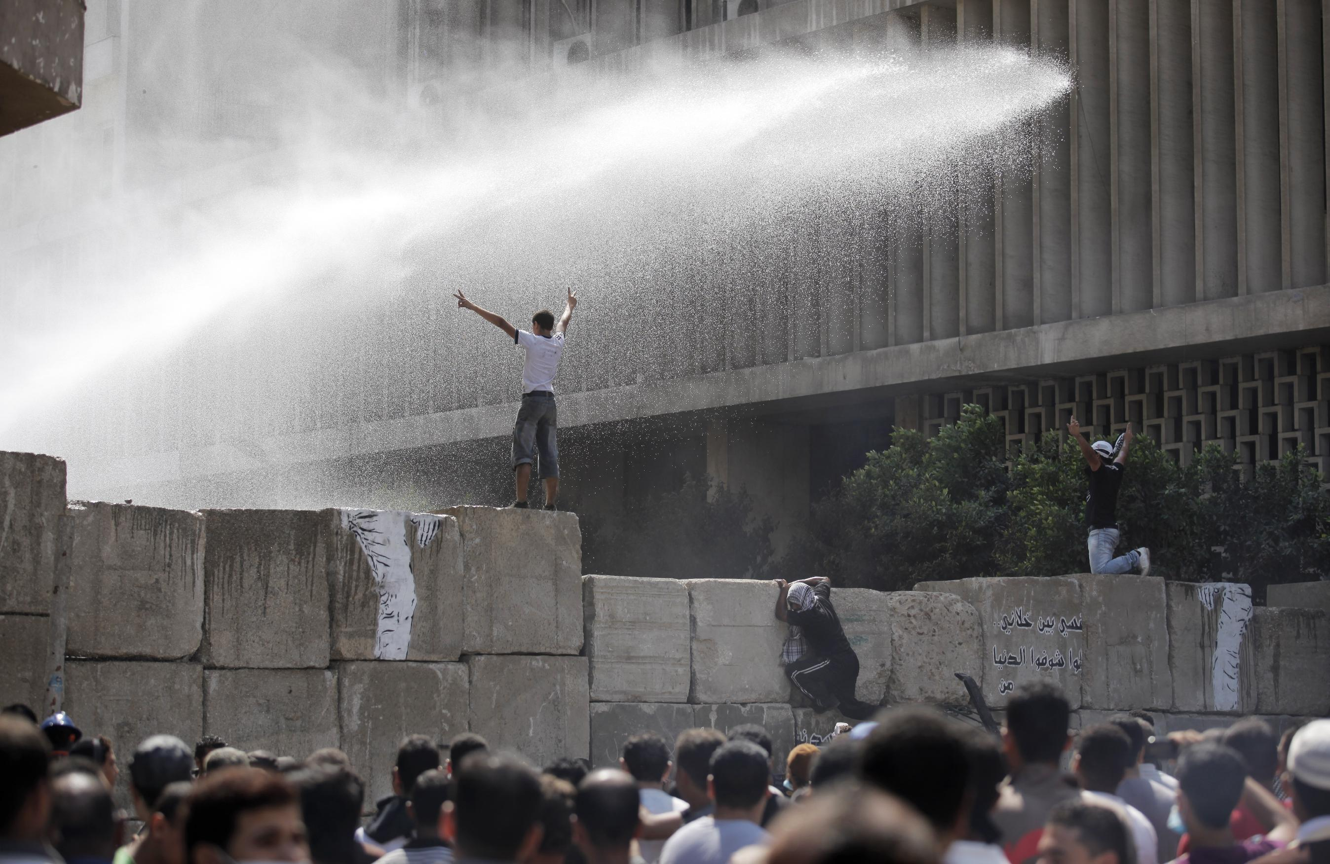 Egyptian security forces use water cannons against protesters, some climbing cement blocks that are used to close the street leading to the U.S. embassy, during clashes in Cairo, Egypt, Friday, Sept. 14, 2012, as part of widespread anger across the Muslim world about a film ridiculing Islam's Prophet Muhammad. (AP Photo/Nasser Nasser)