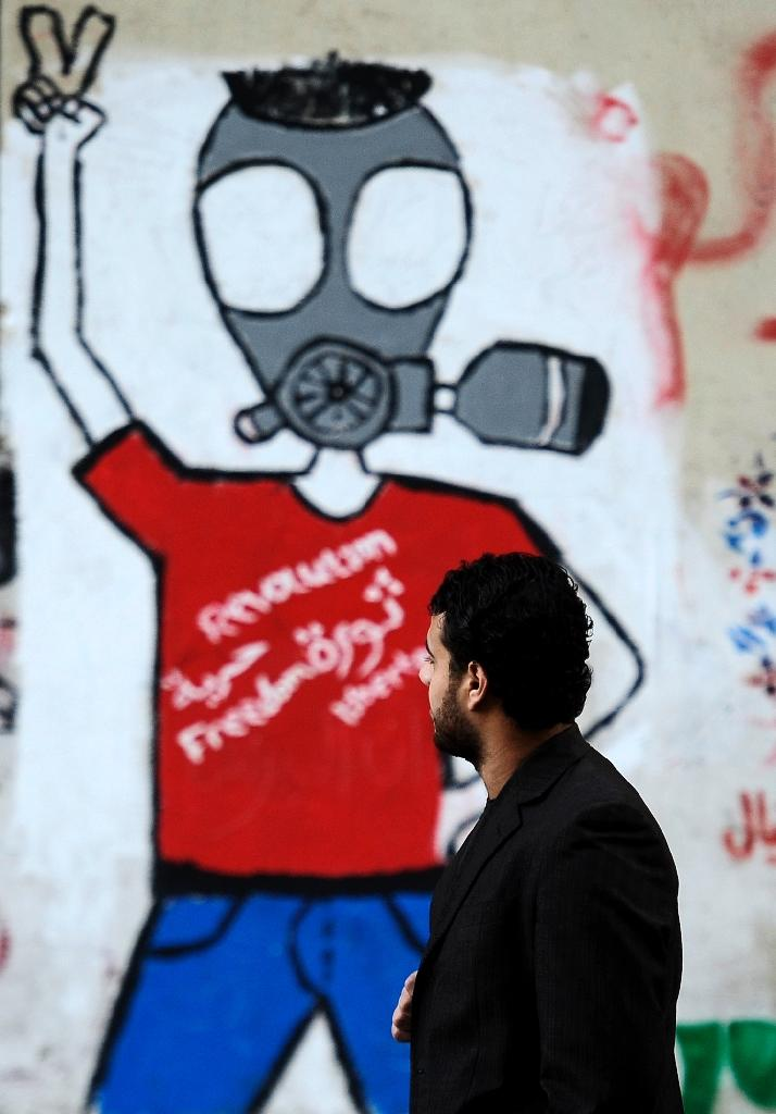 Political graffiti painted on a wall along a road leading to Cairo's Tahrir Square in December 2011 (AFP Photo/Filippo Monteforte)
